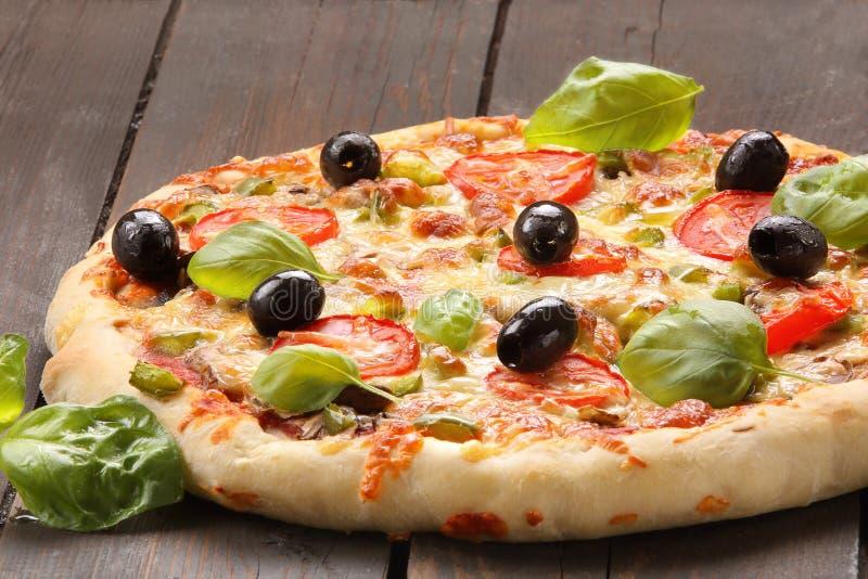 Pizza com tomates, azeitonas e manjericão no fundo de madeira foto de stock