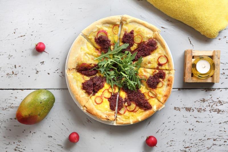 Pizza com vegetais e molho de tomate com folhas do foguete foto de stock