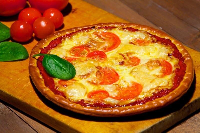 Pizza com vegetais em uma placa de madeira velha foto de stock royalty free