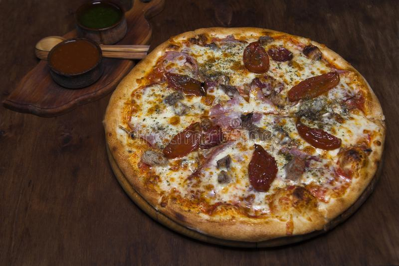 Pizza com vitela, presunto, queijo e os tomates sol-secados imagem de stock