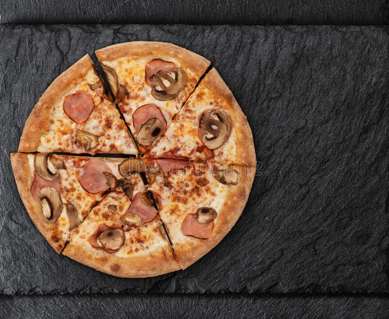 Pizza con champiñones y jamón en pizarra fotografía de archivo libre de regalías