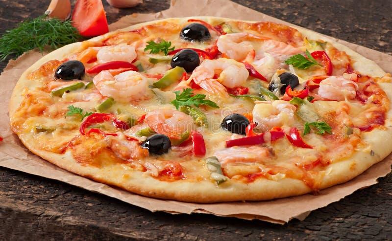 Pizza con el camarón, los salmones y las aceitunas imagen de archivo