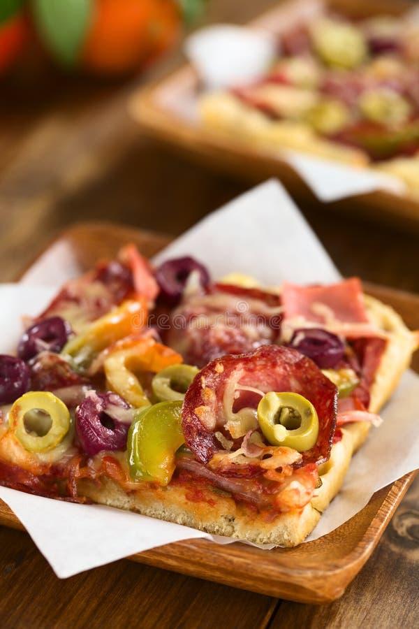Pizza con el jamón, el salami, la aceituna y la pimienta imagen de archivo
