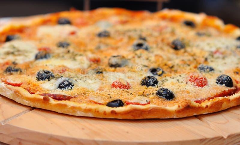 Pizza con el jamón, la pimienta, el tomate y las aceitunas imagenes de archivo