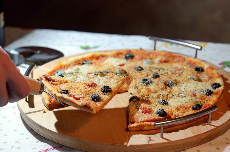 Pizza con el jamón, la pimienta, el tomate y las aceitunas imagen de archivo