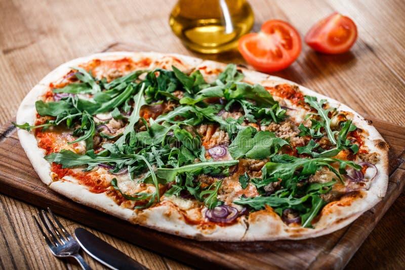 Pizza con el pollo, el arugula, el queso y cebollas en la tabla rústica de madera fotografía de archivo