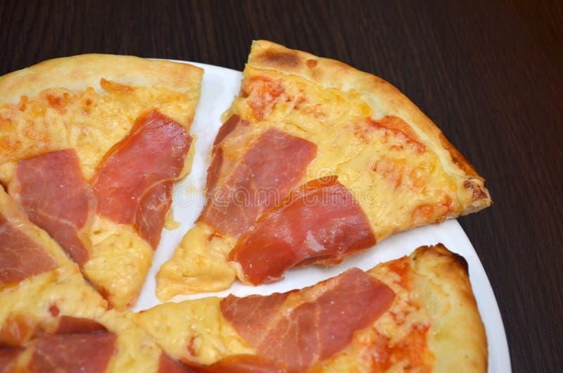 Pizza con el queso y el prosciutto en una placa blanca en una tabla de madera oscura, una pieza cortada fotografía de archivo