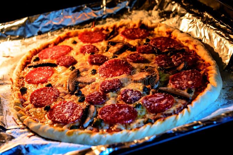 pizza con el salami, el queso y la seta en la estufa fotografía de archivo