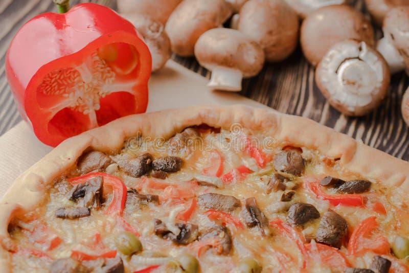 Pizza con i funghi e con formaggio casalingo su una tavola di legno immagini stock libere da diritti