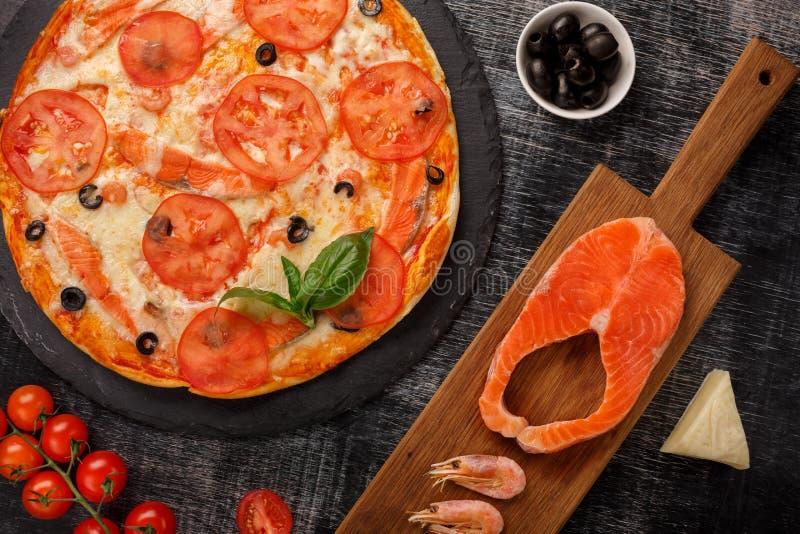 Pizza con i gamberetti, il raccordo di color salmone ed il formaggio Nutriente, utile Vista superiore Priorità bassa nera fotografia stock libera da diritti