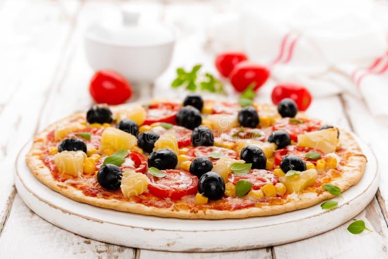 Pizza con i pomodori, il formaggio della mozzarella, le olive, il cereale ed il basilico Cucina italiana tradizionale immagine stock libera da diritti