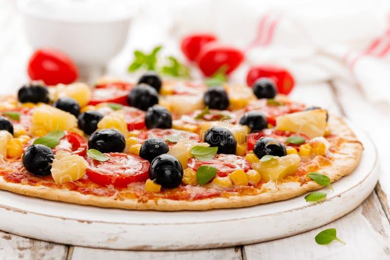 Pizza con i pomodori, il formaggio della mozzarella, le olive, il cereale ed il basilico Cucina italiana tradizionale immagini stock libere da diritti