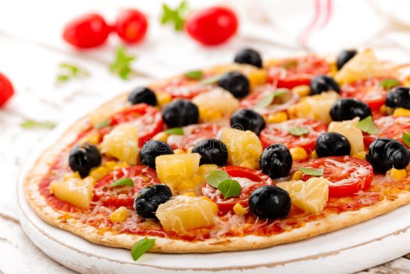 Pizza con i pomodori, il formaggio della mozzarella, le olive, il cereale ed il basilico Cucina italiana tradizionale fotografia stock