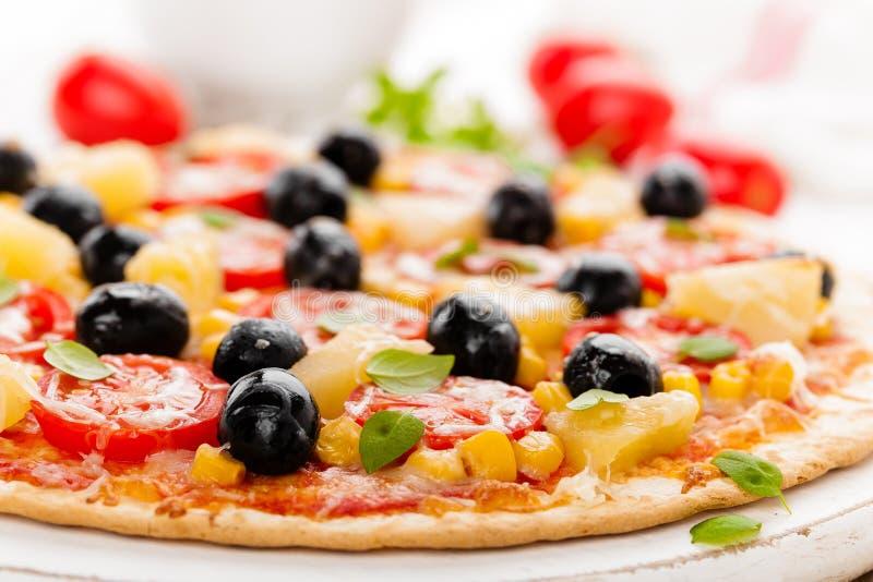 Pizza con i pomodori, il formaggio della mozzarella, le olive, il cereale ed il basilico Cucina italiana tradizionale fotografie stock