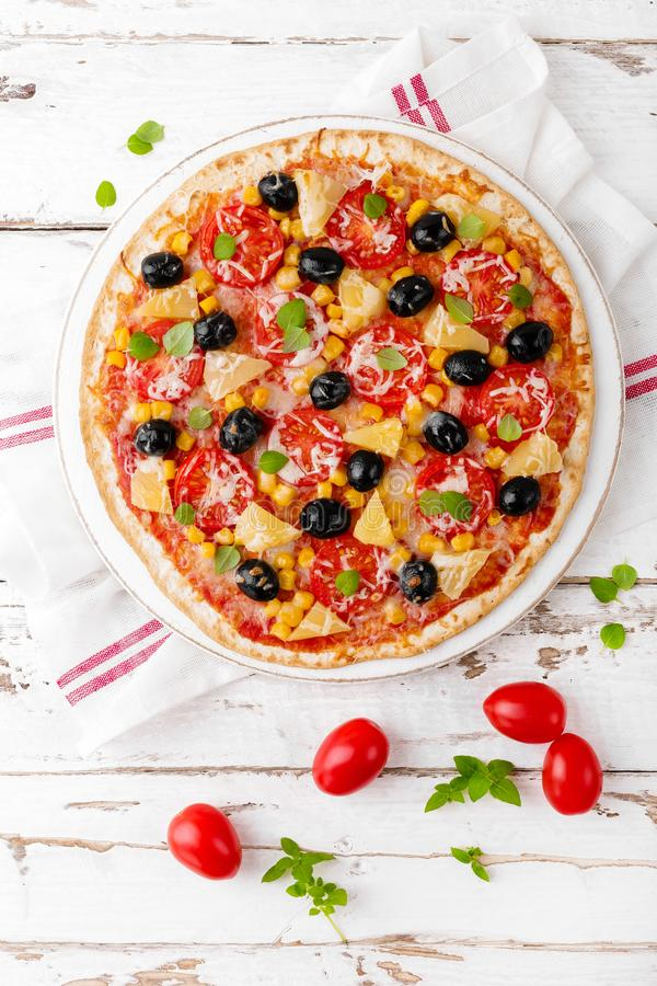 Pizza con i pomodori, il formaggio della mozzarella, le olive, il cereale ed il basilico Cucina italiana tradizionale Vista super fotografie stock