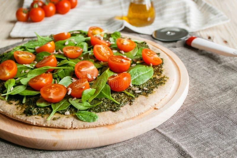 Pizza con il pesto, gli spinaci ed i pomodori ciliegia fotografia stock libera da diritti