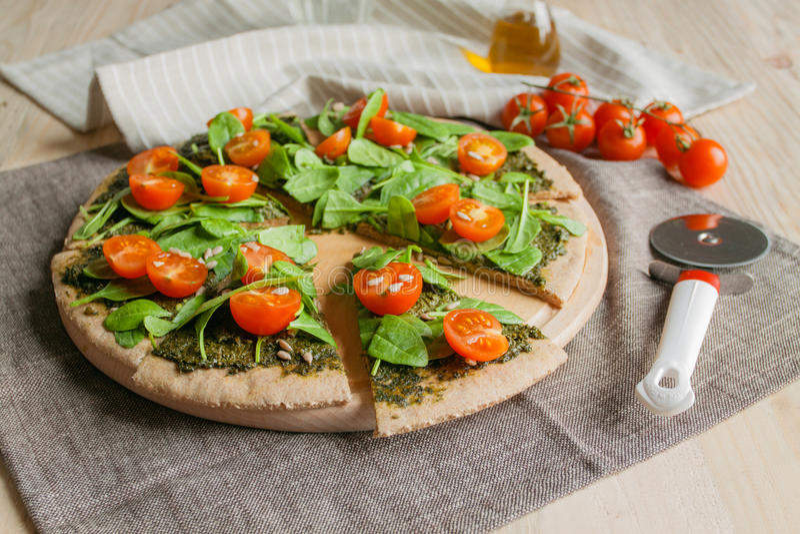 Pizza con il pesto, gli spinaci ed i pomodori ciliegia immagine stock libera da diritti