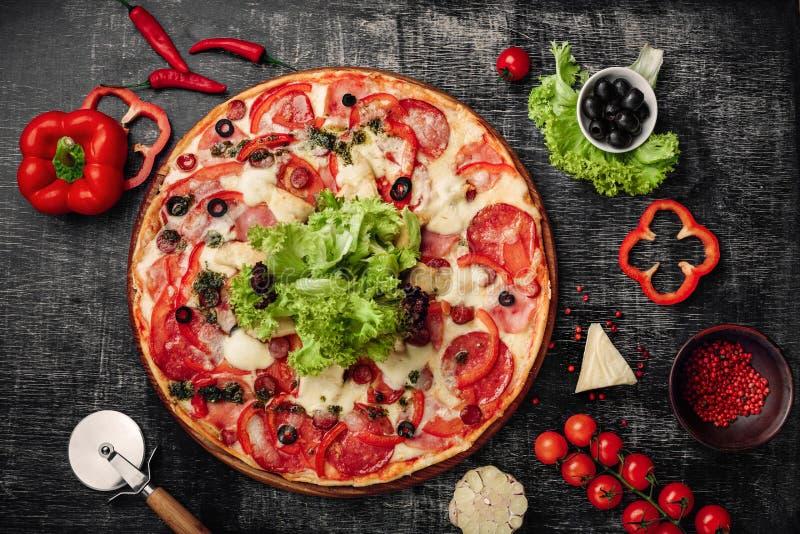 Pizza con il prosciutto, il salame, il formaggio, i funghi, i pomodori ciliegia, i peperoni dolci e l'insalata su un bordo di ges immagini stock