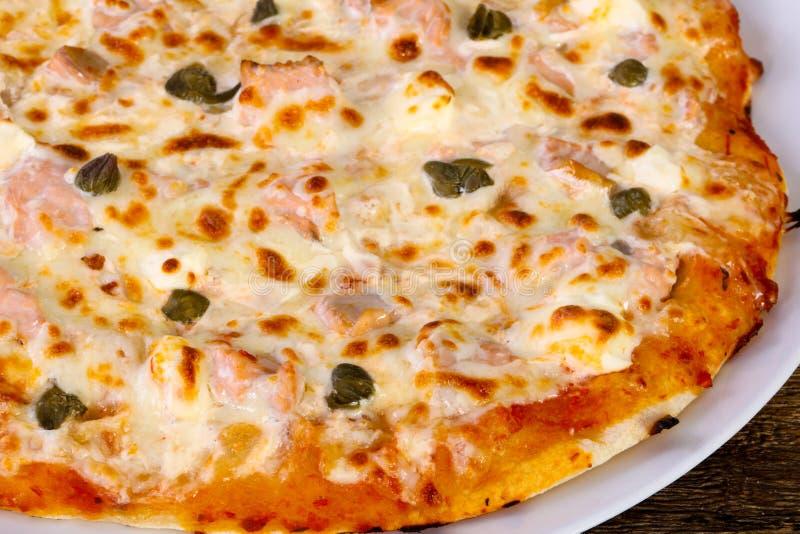 Pizza con il salmone ed i capperi fotografia stock