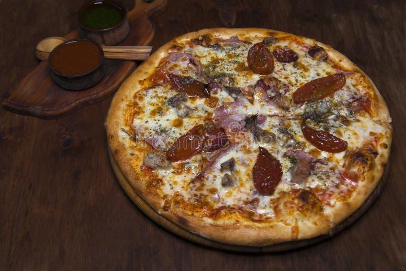 Pizza con il vitello, il prosciutto, il formaggio ed i pomodori seccati al sole immagine stock