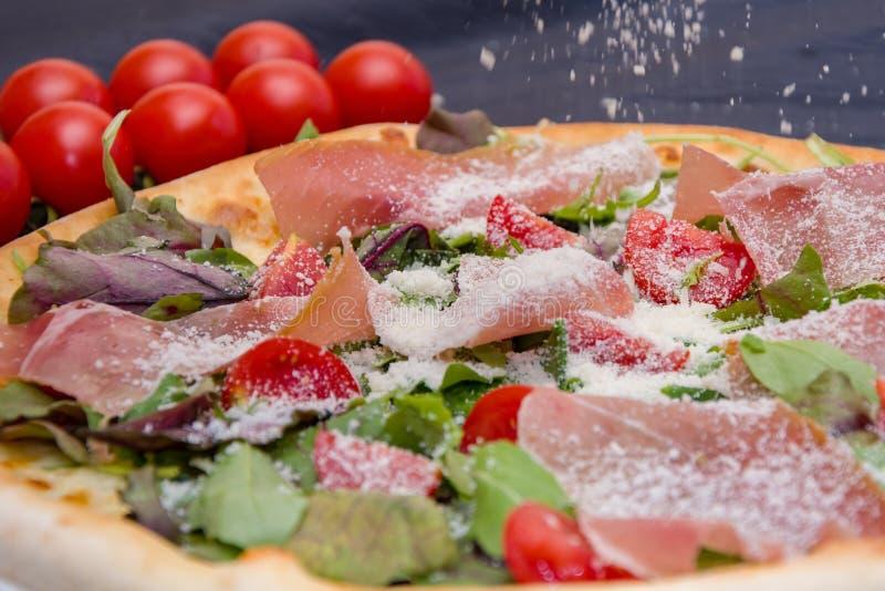 Pizza con la carne y las hierbas, asperjadas con queso, tomates de cereza fotos de archivo