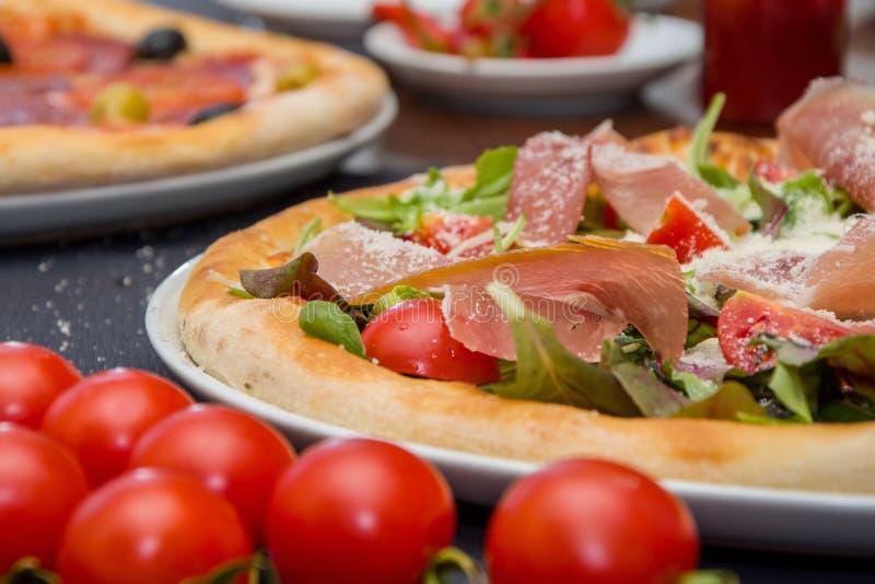 Pizza con la carne y las hierbas, asperjadas con queso, tomates de cereza imagen de archivo