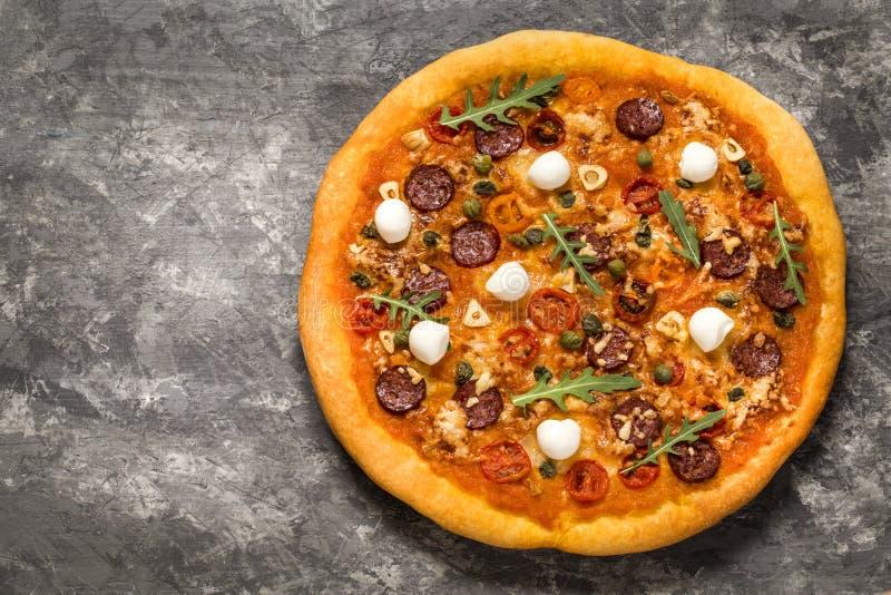 Pizza con la mozzarella, i capperi, i pomodori e la rucola immagini stock libere da diritti