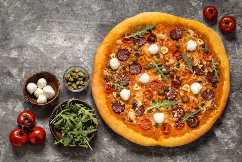 Pizza con la mozzarella, i capperi, i pomodori e la rucola fotografia stock libera da diritti