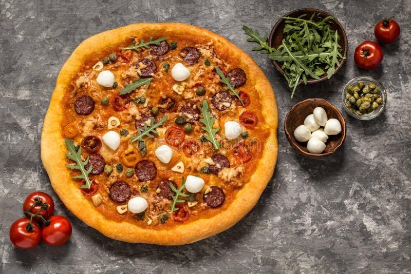 Pizza con la mozzarella, i capperi, i pomodori e la rucola immagine stock