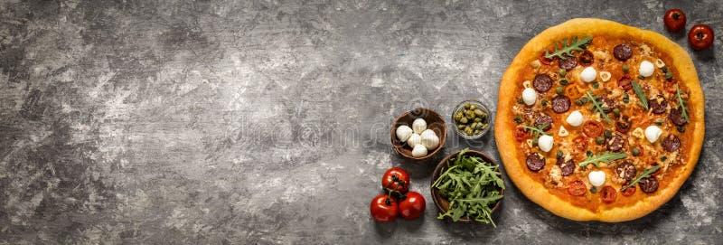 Pizza con la mozzarella, i capperi, i pomodori e la rucola fotografia stock