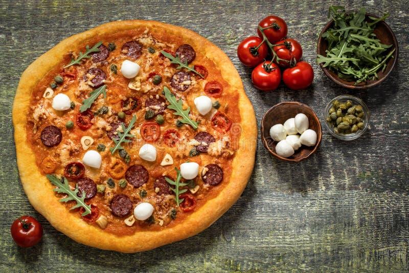 Pizza con la mozzarella, i capperi, la rucola ed i pomodori su fondo di legno fotografia stock libera da diritti