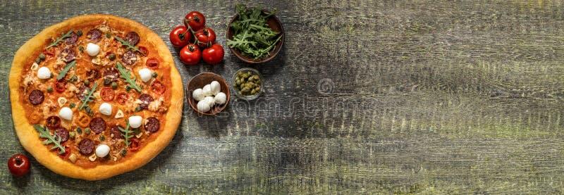 Pizza con la mozzarella, i capperi, la rucola ed i pomodori su fondo di legno immagini stock