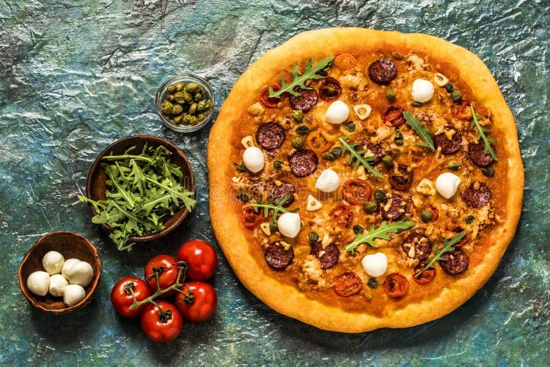 Pizza con la mozzarella, i capperi, la rucola ed i pomodori su un fondo blu fotografie stock