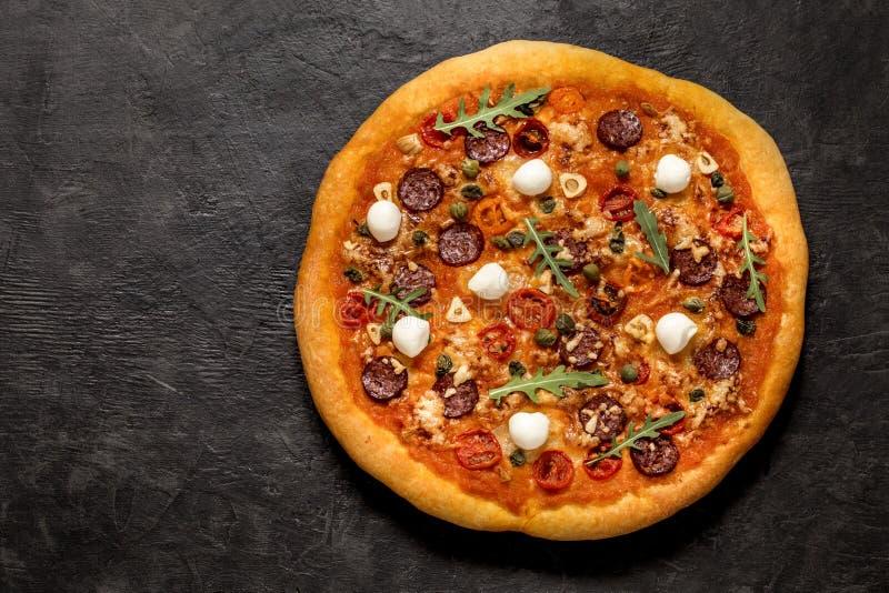 Pizza con la mozzarella, i capperi, la rucola ed i pomodori su un fondo nero immagini stock libere da diritti
