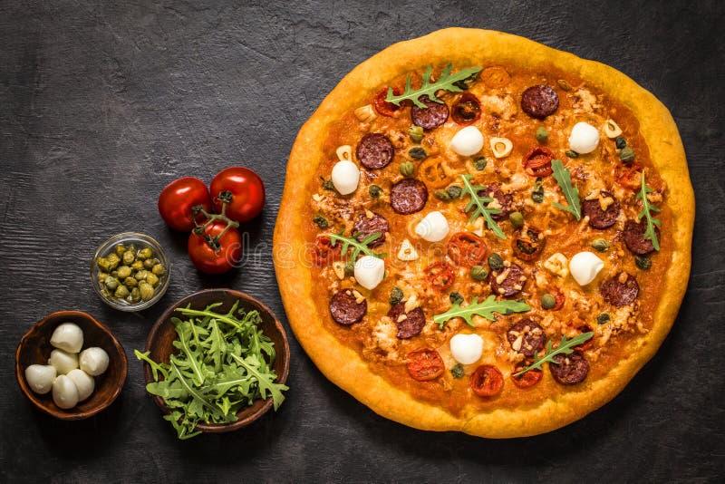 Pizza con la mozzarella, i capperi, la rucola ed i pomodori su un fondo nero immagini stock