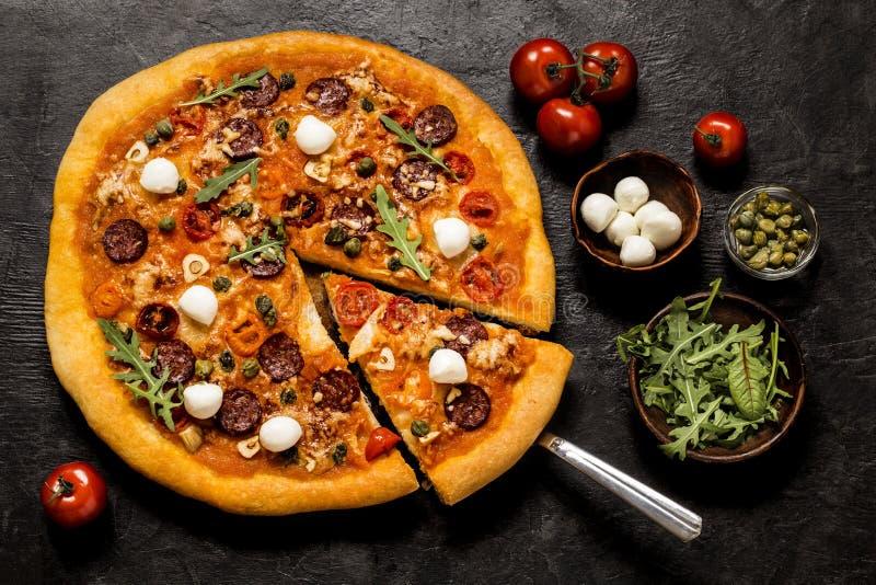 Pizza con la mozzarella, i capperi, la rucola ed i pomodori su un fondo nero immagine stock libera da diritti