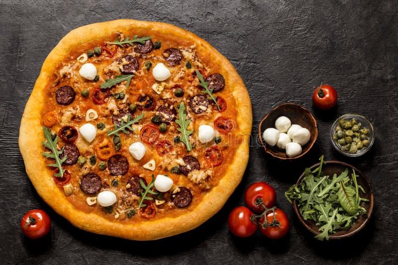 Pizza con la mozzarella, i capperi, la rucola ed i pomodori su un fondo nero fotografie stock libere da diritti