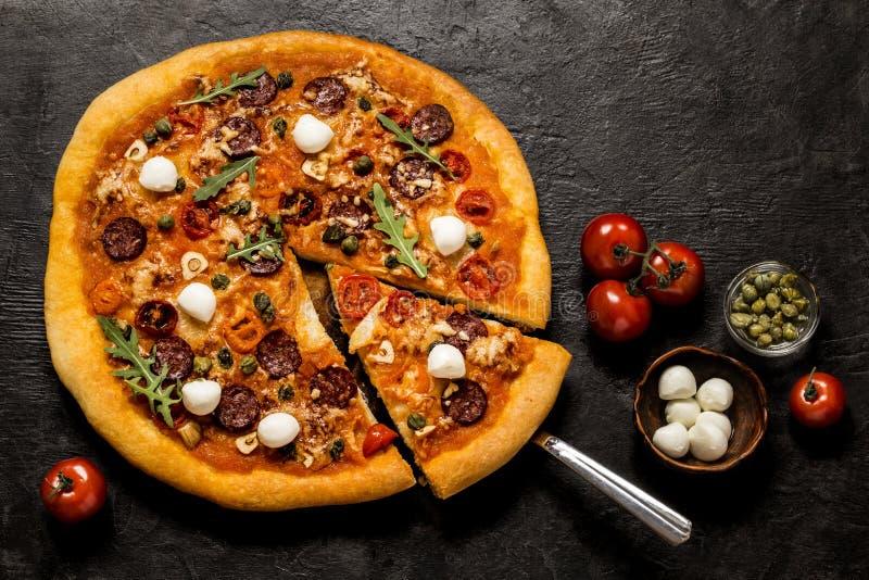 Pizza con la mozzarella, i capperi, la rucola ed i pomodori su un fondo nero immagine stock