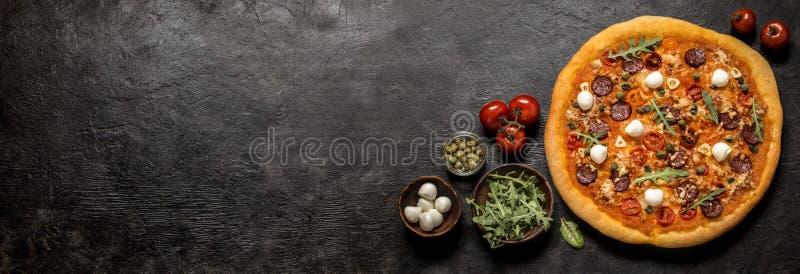 Pizza con la mozzarella, i capperi, la rucola ed i pomodori su un fondo nero fotografia stock