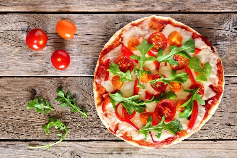 Pizza con la rucola ed i pomodori ciliegia contro legno rustico fotografia stock