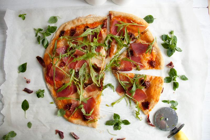 Pizza con la salsa de tomate, el prosciutto y el arugula imágenes de archivo libres de regalías