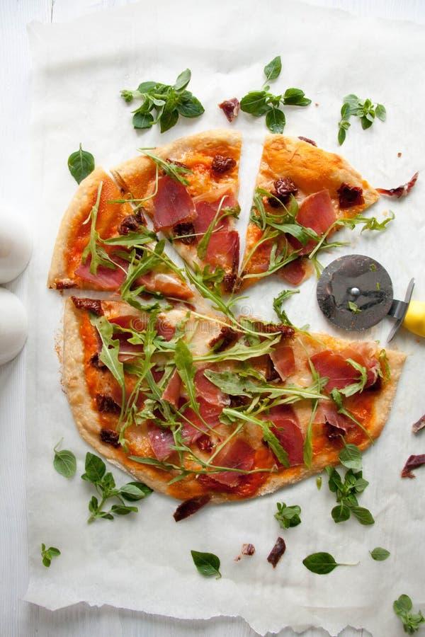 Pizza con la salsa de tomate, el prosciutto y el arugula foto de archivo libre de regalías
