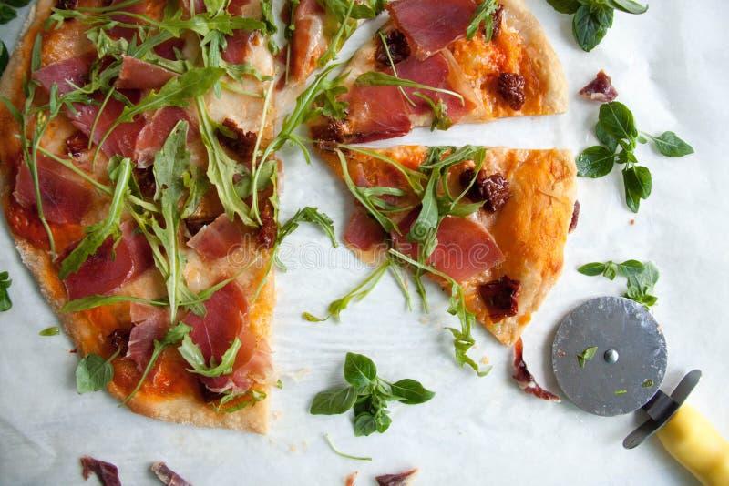 Pizza con la salsa de tomate, el prosciutto y el arugula imagen de archivo libre de regalías