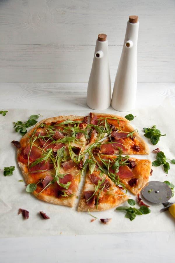 Pizza con la salsa de tomate, el prosciutto y el arugula fotos de archivo libres de regalías