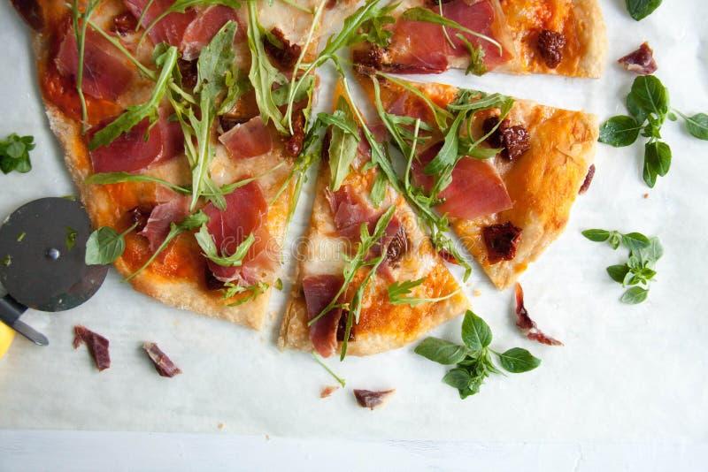 Pizza con la salsa de tomate, el prosciutto y el arugula fotografía de archivo