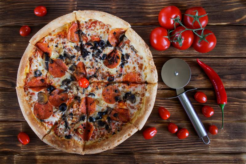 Pizza con le bugie delle merguez, del salame, dei funghi e delle olive su una tavola rustica accanto a peperone, ai pomodori e ad immagini stock libere da diritti