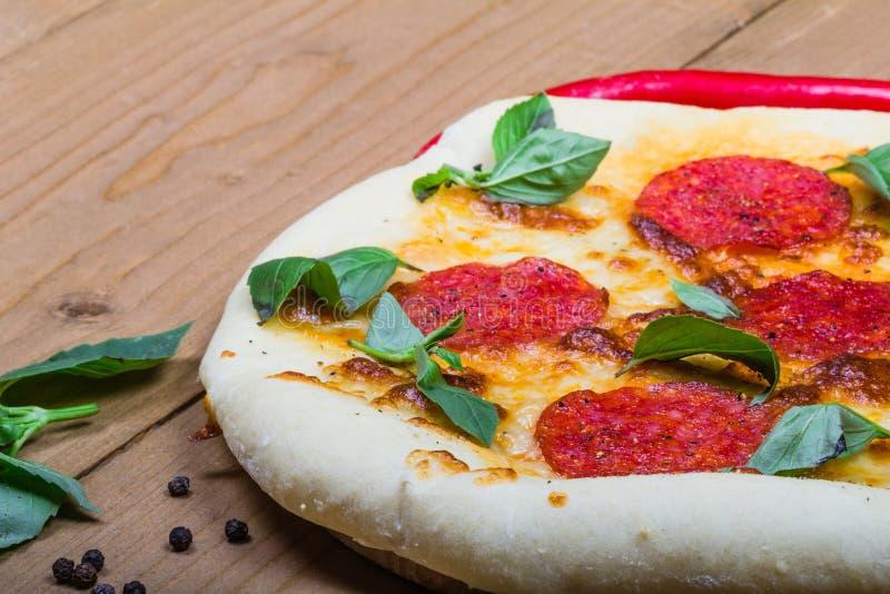 Pizza con le merguez su fondo di legno immagini stock