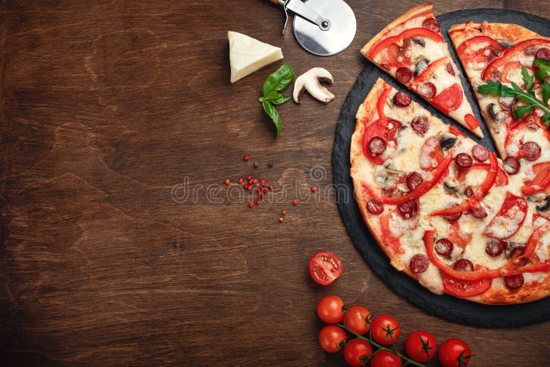 Pizza con le salsiccie affumicate, il formaggio, i funghi, i pomodori, i peperoni dolci su una pietra e un bordo marrone di legno immagine stock
