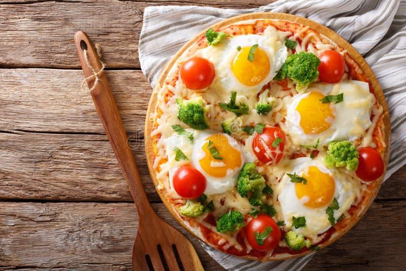 Pizza con le uova, il formaggio, i broccoli, i pomodori ed il primo piano delle erbe fotografia stock