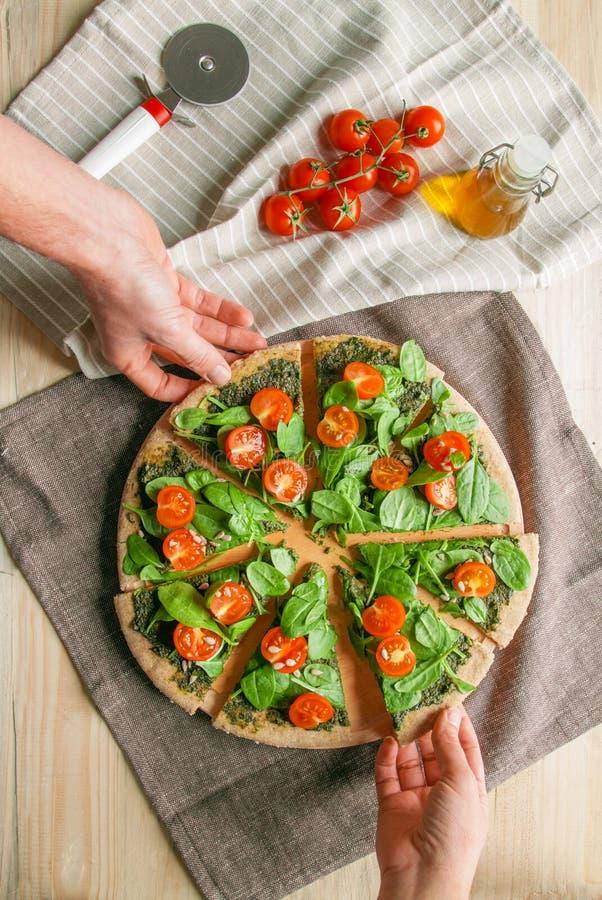 Pizza con los tomates del pesto, de la espinaca y de cereza fotografía de archivo libre de regalías